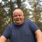 Lee Stanway smiling at camera with trees in background