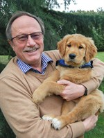 Bill Thornton sitting and holding a golden retriever puppy.