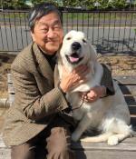 Kazumasda Oda sitting and smiling with a yellow lab.