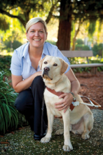 Susan Armstrong in a park kneeling next to a yellow lab wearing a walking harness.