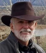Wells Jones in Cowboy hat outside smiling
